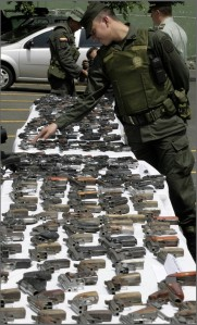 A Colombian police officer looks at weapons confiscated in Cali